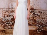 a romantic wedding dress with lace sleeves, a draped bodice, an empire waist and a pleated skirt