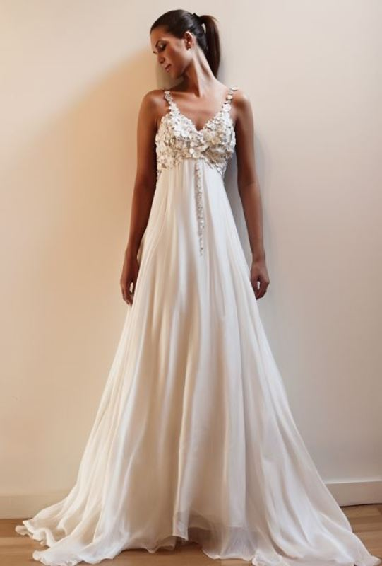 a statement empire waist wedding dress with a floral applique bodice, a pleated skirt and embellished straps