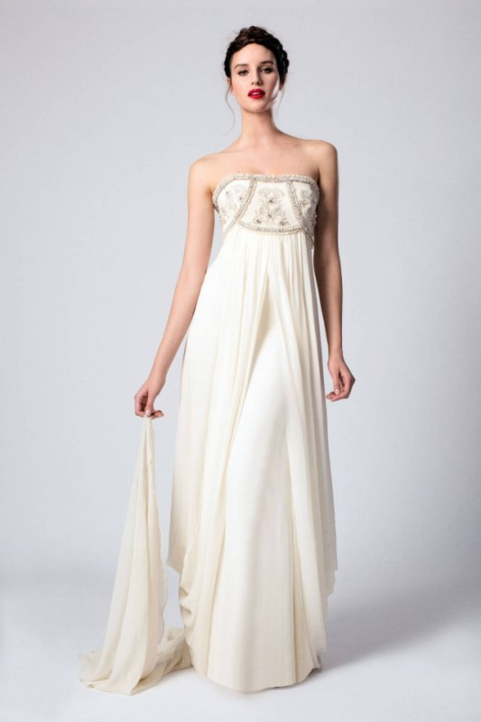 a strapless empire waist wedding dress with an embroidered and embellished bodice and a draped skirt with a train