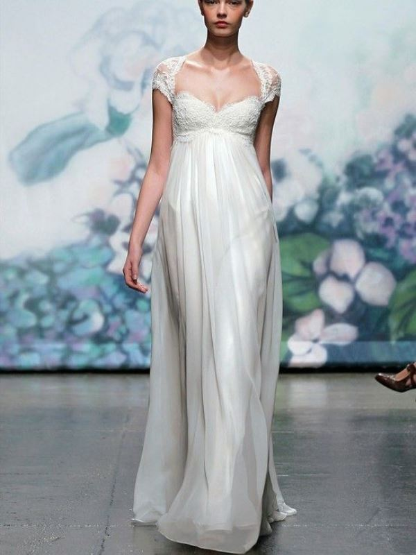 an A line empire waist wedding dress with a lace bodice, lace cap sleeves and a pleated skirt