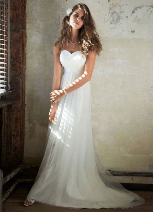 a strapless A-line empire waist wedding dress with a draped bodice and pleated skirt with a train is simple and chic