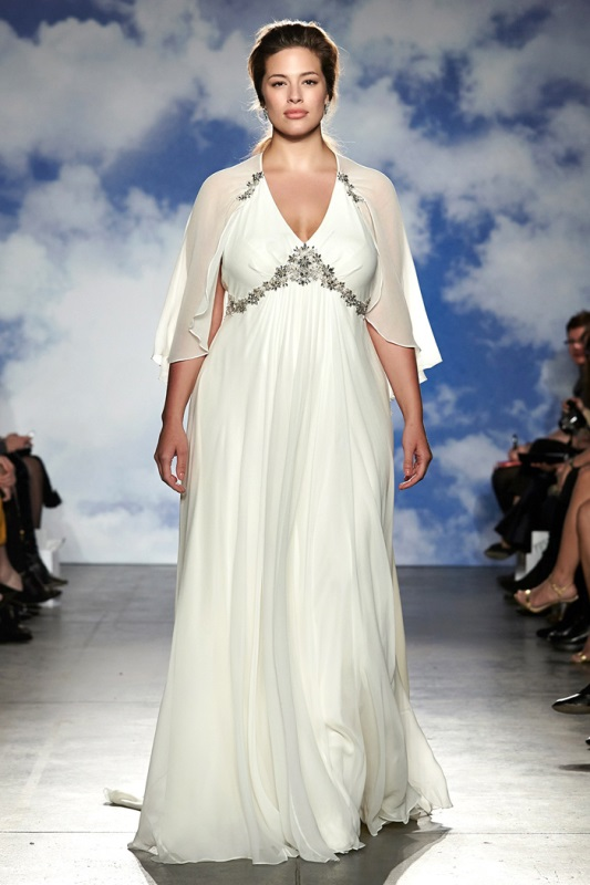 a plus size A line wedding dress with an embellished bodice, a pleated skirt and a capelet