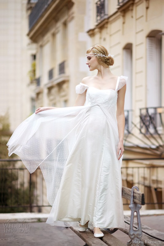 a romantic A line wedding dress with an empire waist, cap sleeves, draped layered skirt with polka dots