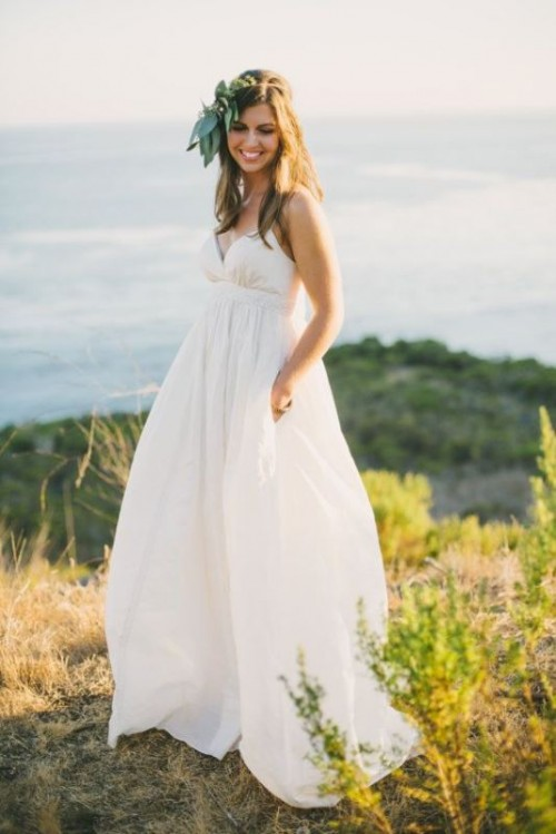 a minimalist empire waist wedding dress with spaghetti straps, a draped bodice and pleated skirt for a modern wedding