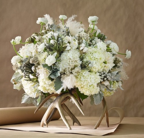a unique winter wedding centerpiece of white blooms, pale greenery placed on gilded antlers is a very stylish and chic idea