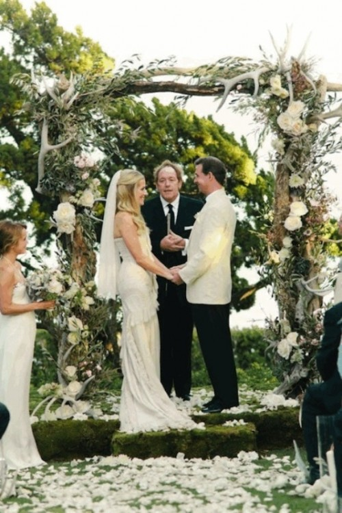 a wedding arch decorated with white blooms, olive branches and antlers is a stylish decoration to rock