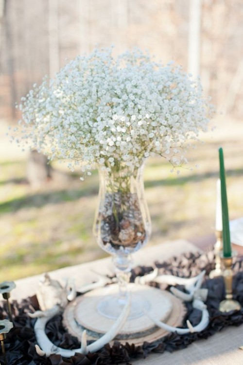 a pretty winter wedding centerpiece of a black table runner, a wood slice, a vase with pinecones and baby's breath is very chic