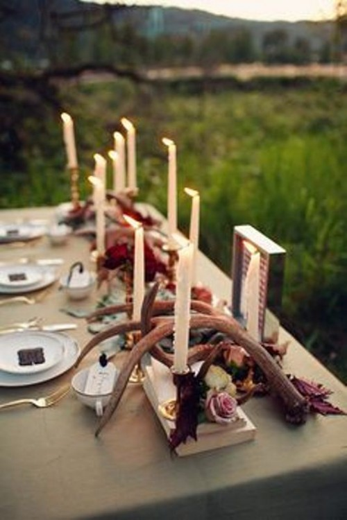 a flower and candle centerpiece paired with antlers looks much more interesting and catchy and feels more woodland-like