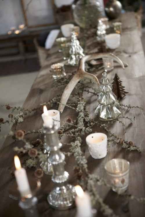 a winter wedding table decorated with candles in mercury glass candleholders, pinecones and antlers is a beautiful decadent-like idea