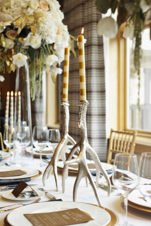 antlers as candleholders and striped candles to decorate a winter wedding table
