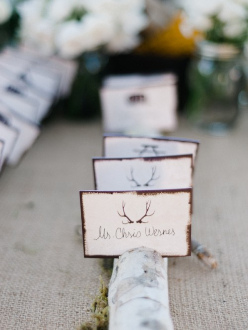 moss, a branch and some cards with antlers look cool and woodland-like and bring that cozy feel to your wedding