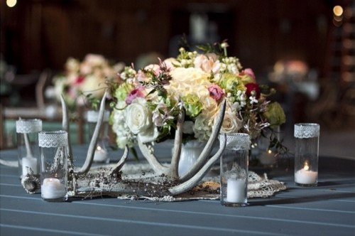 a refined winter wedding centerpiece of beautiful blooms, candles in glasses and antlers feels very woodland-like and very chic