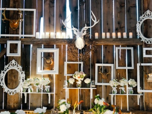 a bold rustic gallery wall of empty frames, blooms and faux taxidermy is a creative idea to decorate your wedding venue