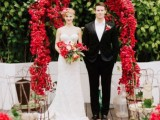 a bright red floral wedding arch and matching floral arrangements in bottles and vases for a colorful summer wedding