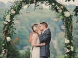 a beautiful wedding arch covered with greenery and white blooms and hanging candleholders is amazing