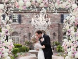 a lush and beautiful wedding arch covered with light pink and white blooms and a crystal chandelier is a stylish and chic idea