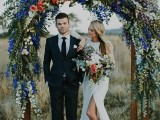 a bright wedding arch covered with white, electric blue blooms, purple and coral ones and eucalyptus is wow