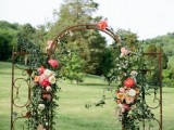 a refined vintage wedding arch made of a vintage gate, with greenery, neutral, peachy and pink blooms is chic