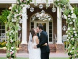 a catchy wedding arch covered with greenery, white and pink blooms and candles hanging in bulbs is wow