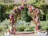 a colorful floral wedding arch with lilac, pink, red blooms and greenery and blue floral arrangements lining up the aisle