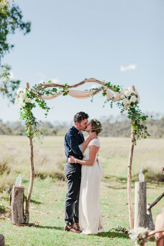 a delicate rustic wedding arch with neutral fabric, greeneyr and white blooms and tree stumps with bottles