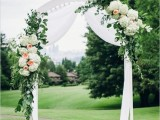 a white wedding arch with white fabric, greenery, white and blush blooms is an elegant and timeless solution