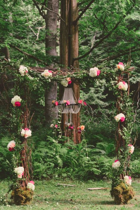 a bold wedding arch of branches and twigs, with moss, white and hot pink blooms and a crystal chandelier with pink flowers