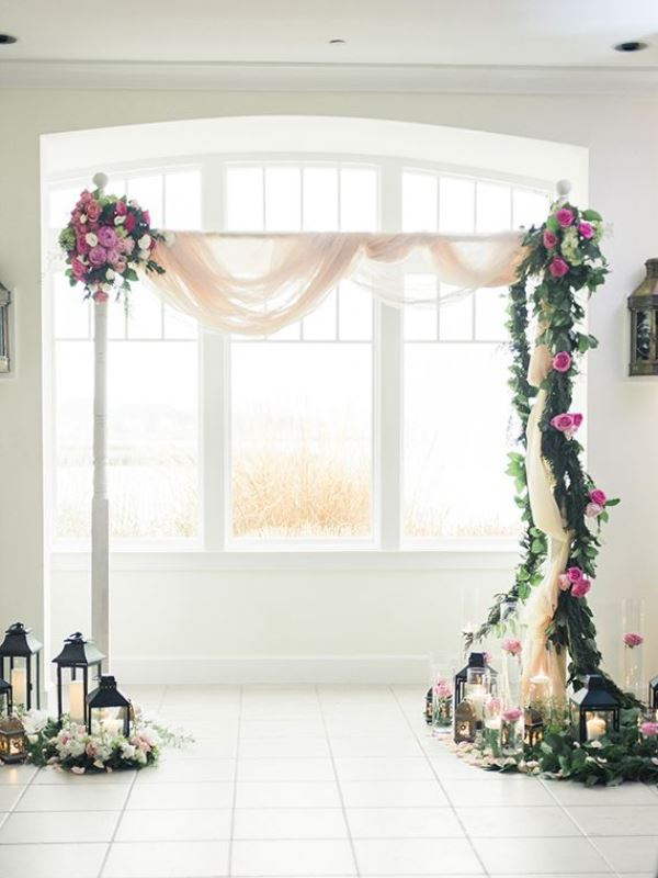 a catchy wedding arch with blush fabric, greenery, white and hot pink blooms and candle lanterns all around
