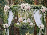 a refined and fairy-tale like wedding arch with greenery, blush blooms, bubbles with candles and hanging grass and candles on the arch
