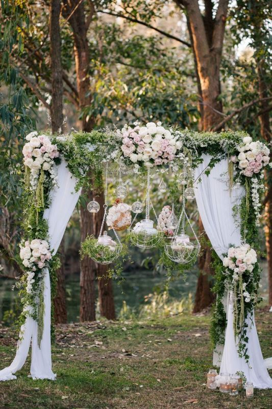 a refined and fairy tale like wedding arch with greenery, blush blooms, bubbles with candles and hanging grass and candles on the arch