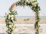 a lovely wedding arch with blush, white blooms, eucalyptus and twigs is a pretty and very romantic idea