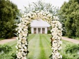 a lush and bold wedding arch covered with white blooms and eucalyptus, with petals on the ground is amazing