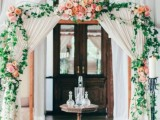 a cool wedding arch done with white fabric, peachy and coral blooms and greenery is a refined and chic option
