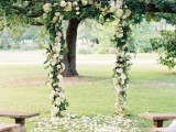 a wedding arch covered with greenery and white blooms and white petals on the ground is a pretty rustic wedding decor idea