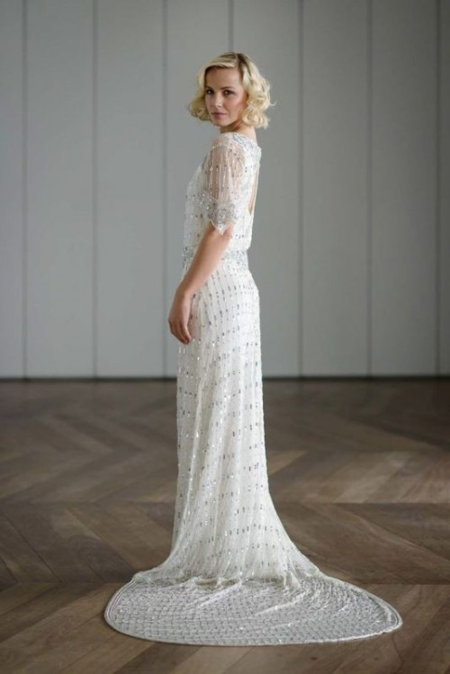 a 20s inspired fitting white fully embellished wedding dress with a keyhole back, short sleeves and a train