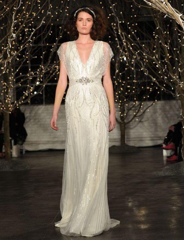a sparkling fully embellished 20s inspired wedding dress with a depe neckline and an embellished sash