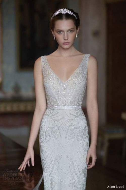a glam fitting white and silver embellished wedding dress with no sleeves and a deep neckline