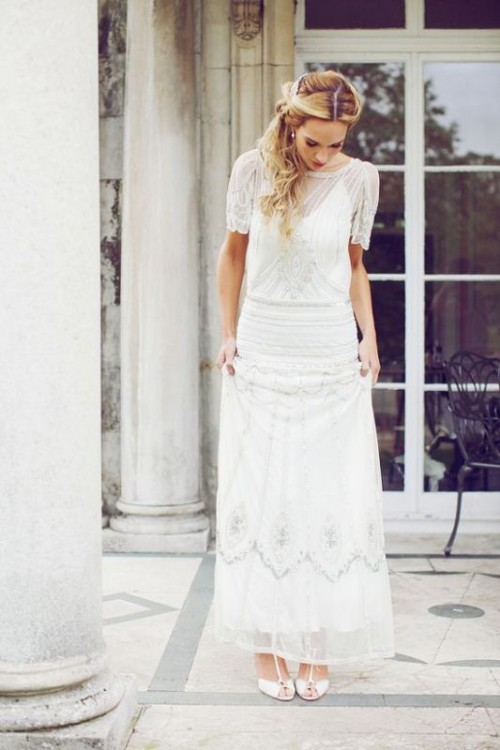 a Great Gatsby inspired fully embellished wedding dress with an illusion neckline, short sleeves and vintage-inspired shoes