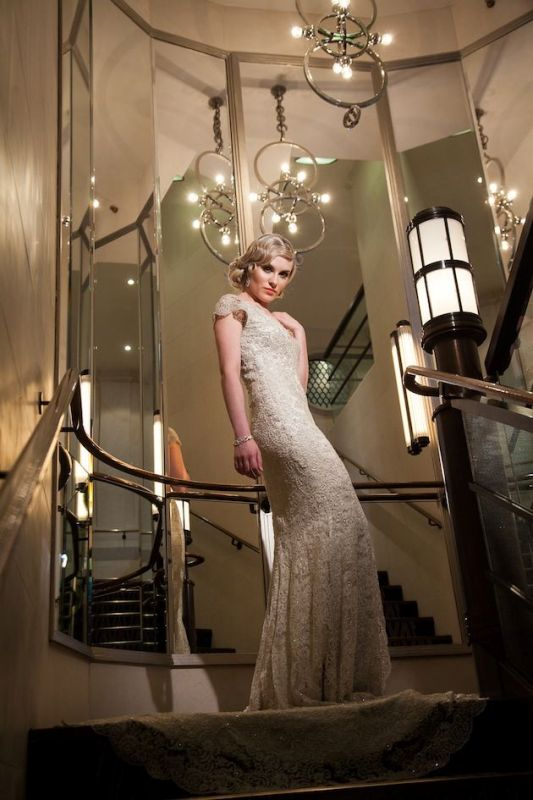a fitting lace wedding dress with a V neckline and cap sleeves and a stylized hairstyle for a Great Gatsby wedding