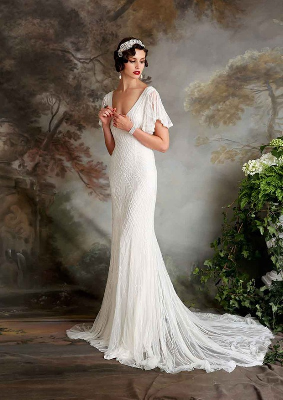 a beautiful fitting 20s wedding dress with patterns and beading, a deep V neckline, cap sleeves and a train