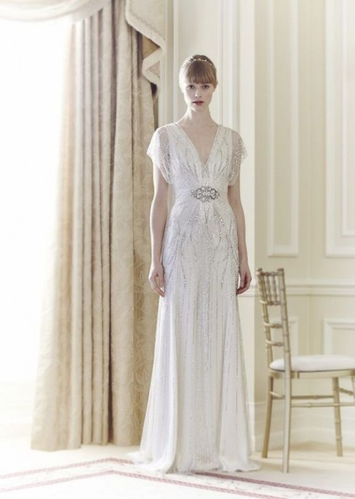 a white 1920s inspired wedding dress with silver embellishments, cap sleeves and an embellished sash