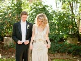 a neutral 1920s inspired wedding dress with gold embellishments, a V-neckline and cap sleeves