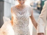 a 1920s inspired fitting wedding dress with no sleeves, a high neckline and full embellishments