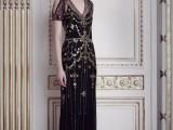 a statement fititng black gold embellished wedding dress with a cold shoulder, a V-neckline