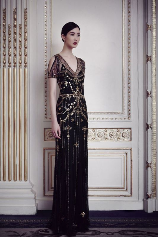 a statement fititng black gold embellished wedding dress with a cold shoulder, a V neckline
