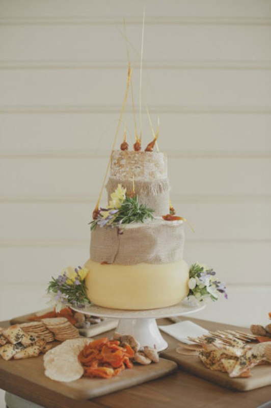 a cheese wheel cake decorated with onions and fresh blooms is a cool substitute for those who don't like sweets