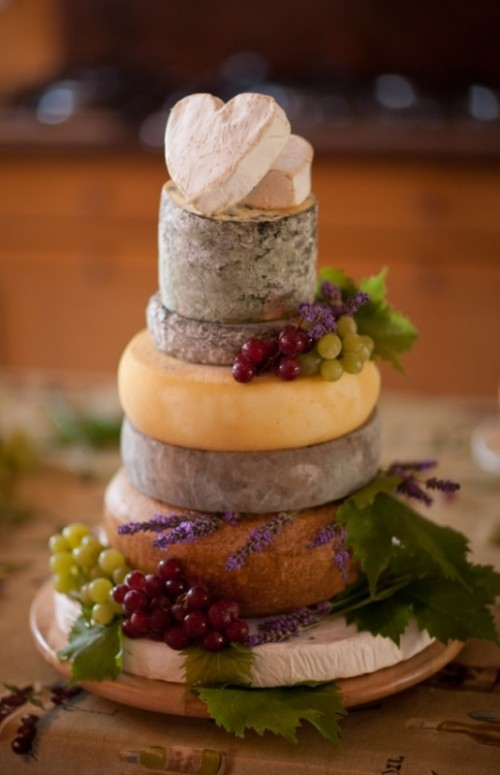 a cheese wheel wedding cake decorated with fresh grapes and greenery will be a nice pair for a glass of wine