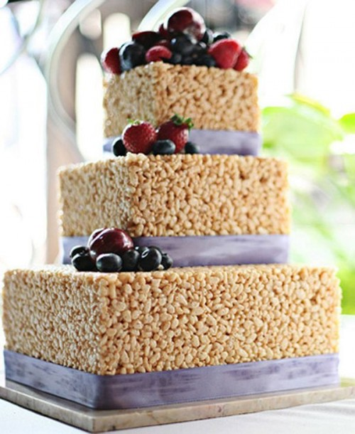 a krispy rice wedding cake topped with fresh berries and fruits and decorated with lilac ribbons
