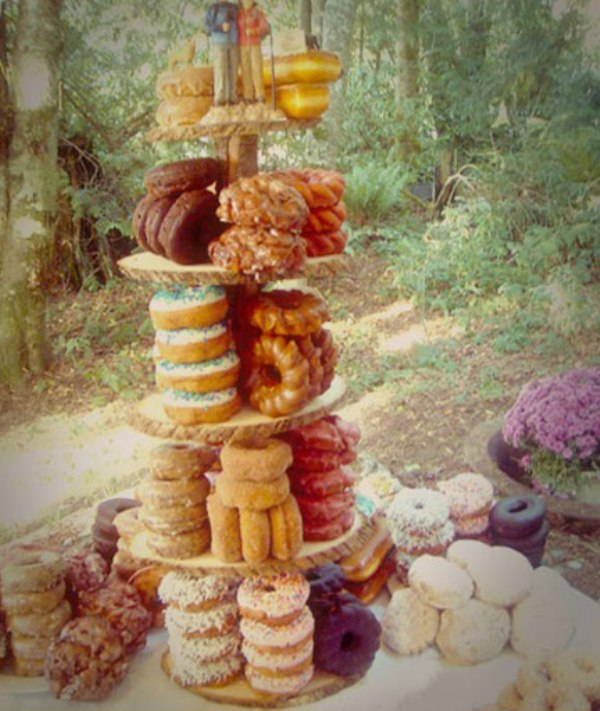 a creative wooden stand with an assortment of glazed donuts for a rustic or woodland wedding