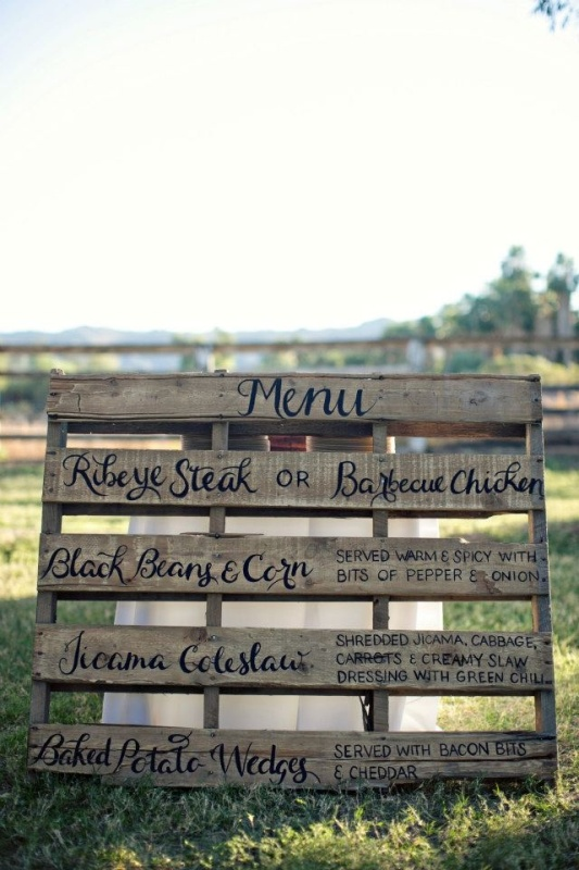 a rustic wedding menu written on a large pallet is a cute idea for a rustic or a backyard wedding